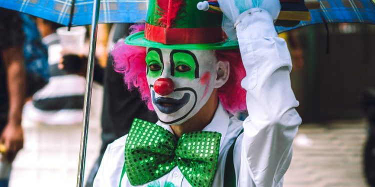funny clown with makeup and costume on street with umbrella