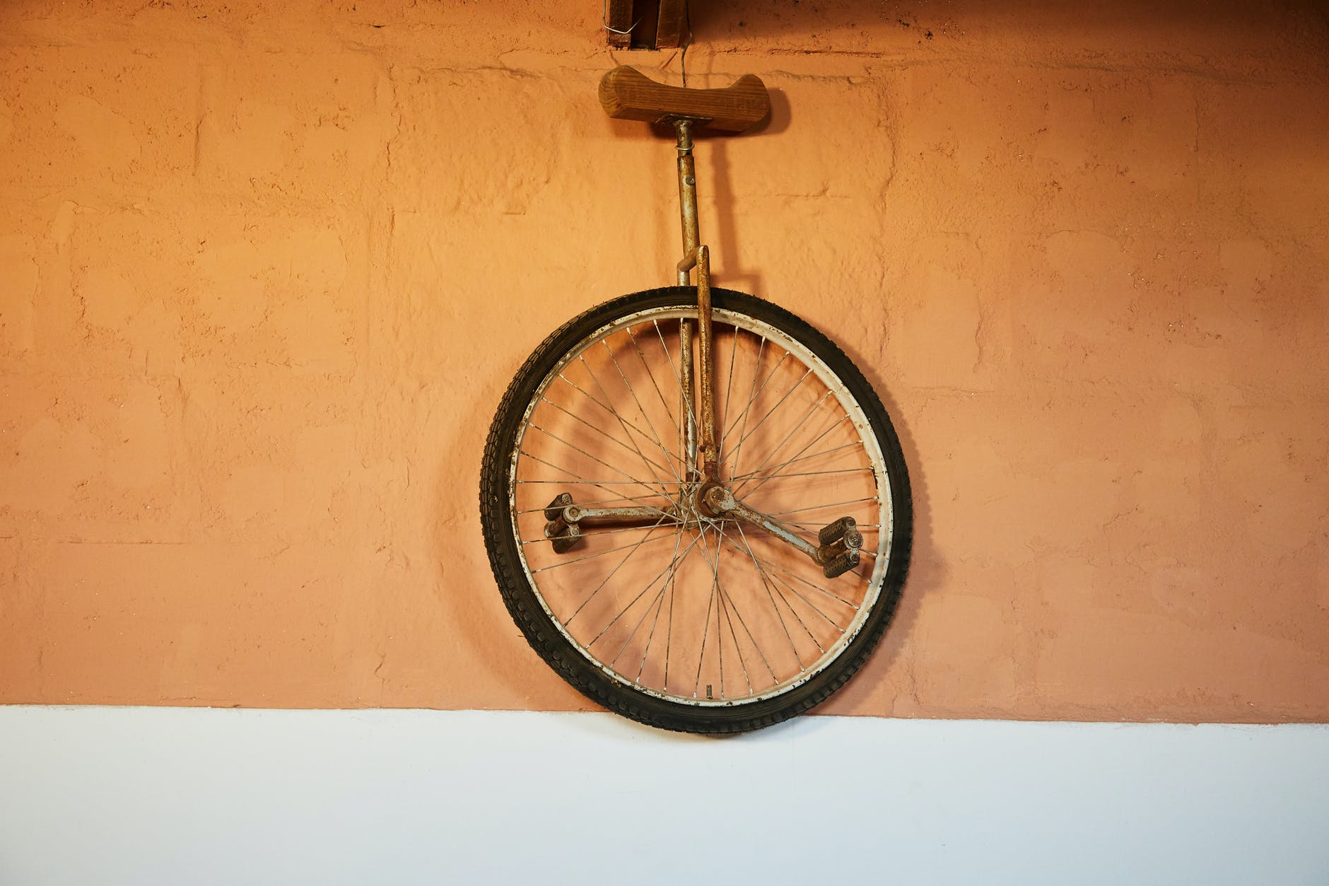 old shabby unicycle hanging on brick wall